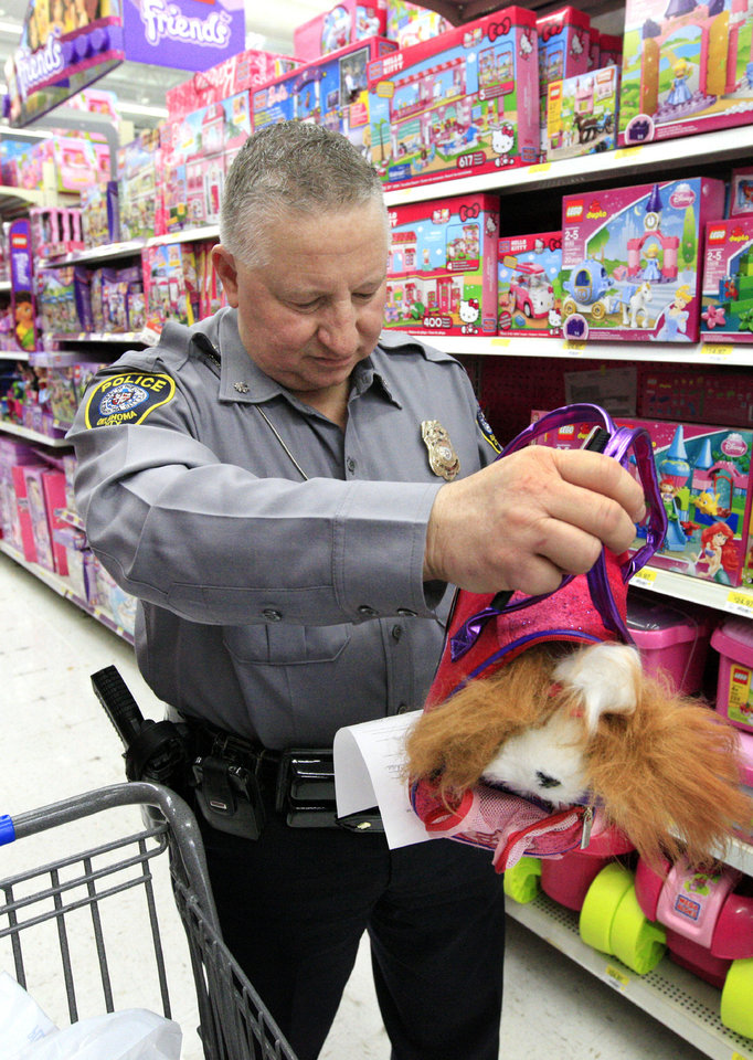 Photo - Oklahoma City Police Department deputy chief John Scully selects a pup-in-a-bag while shopping for Christmas  at a local Wal-Mart store as local law enforcement, in partnership with Sunbeam Family Services, select gifts for the Grandparents Raising Grandchildren Program.  PAUL B. SOUTHERLAND - PAUL B. SOUTHERLAND