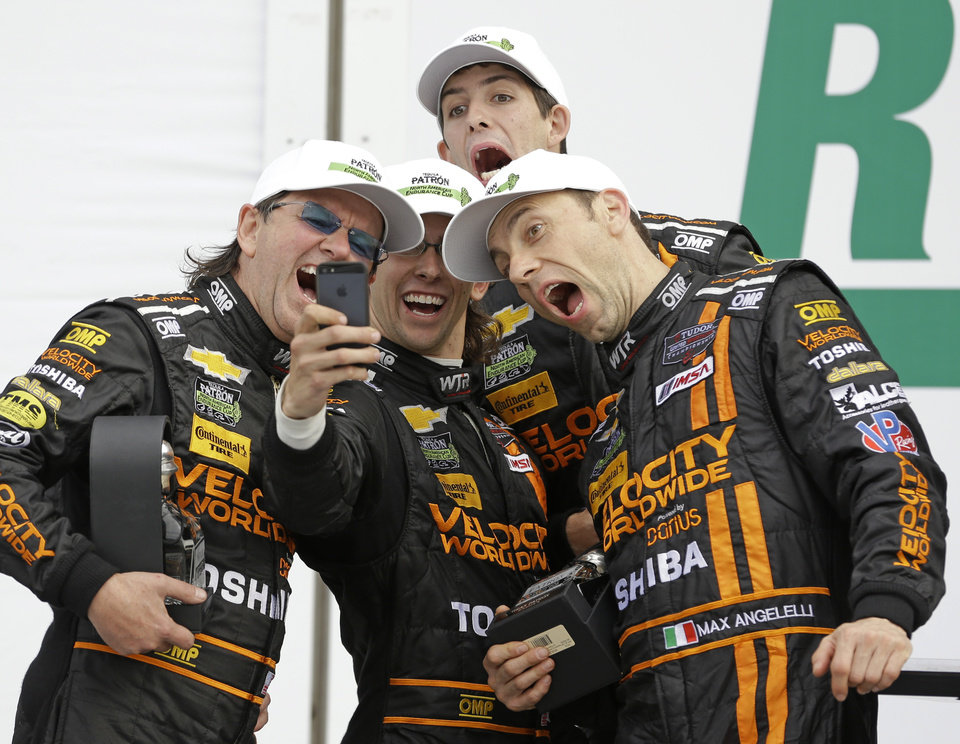 Photo - The Wayne Taylor Racing team, from left, Wayne Taylor, Jordan Taylor, Ricky Taylor and Max Angelelli, of Italy, take a group photo to celebrate their second place finish in the IMSA Series Rolex 24 hour auto race at Daytona International Speedway in Daytona Beach, Fla., Sunday, Jan. 26, 2014.(AP Photo/John Raoux)