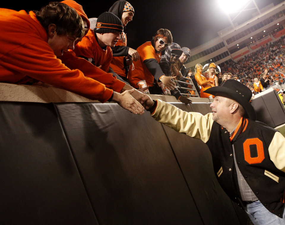 Photo - Garth Brooks shakes hands with fans as he leaves the field at halftime during the college football game between Oklahoma State University (OSU) and the University of Missouri (MU) at Boone Pickens Stadium in Stillwater, Okla. Saturday, Oct. 17, 2009.  Photo by Doug Hoke, The Oklahoman
