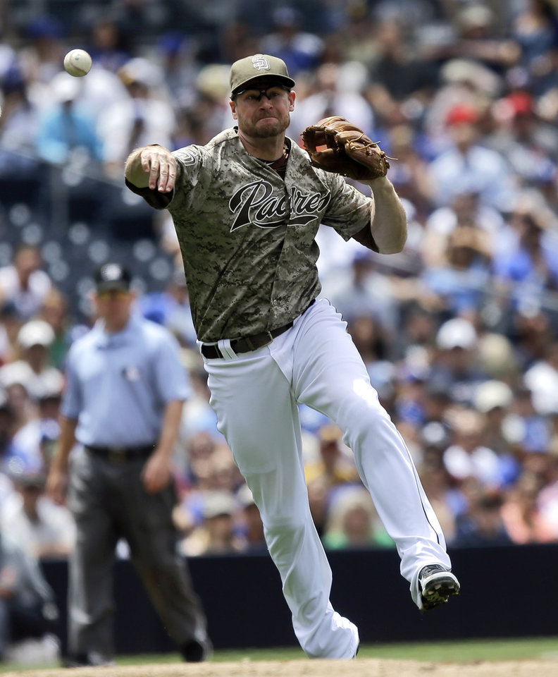 Photo - San Diego Padres third baseman Chase Headley makes the running throw after fielding a slow roller hit by Los Angeles Dodgers' Yasiel Puig in the fourth inning of a baseball game in San Diego, Sunday, June 23, 2013. The throw was wide but Puig was given a hit on the play. (AP Photo/Lenny Ignelzi)