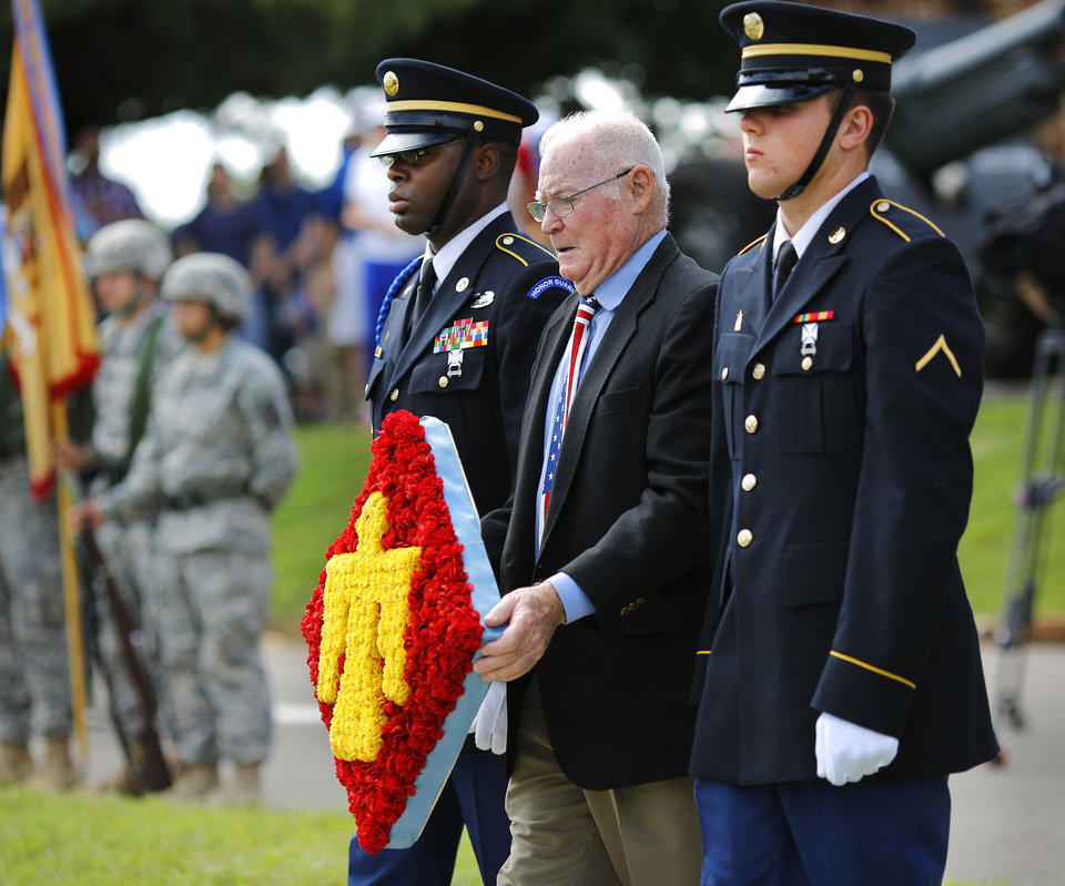 Photo - Preston Willoughby, an executive with the 45th Infantry Division Association, and a Korean War veteran, is escorted by members of the Governor's Honor Guard to place this wreath at the base of the American flag during the 45th Infantry Division Museum's Memorial Day Ceremony on Monday, May 30, 2016. Photo by Jim Beckel, The Oklahoman