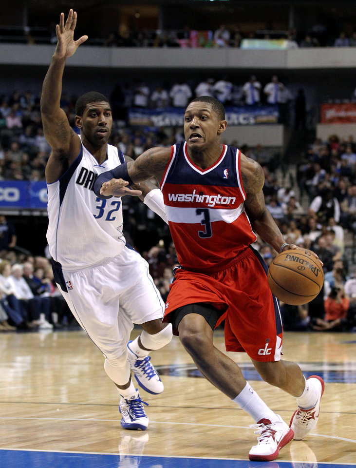 Washington Wizards' Bradley Beal (3) gets by Dallas Mavericks' O.J. Mayo (32) on a drive to the basket for a shot in the first half of an NBA basketball game, Wednesday, Nov. 14, 2012, in Dallas. (AP Photo/Tony Gutierrez)