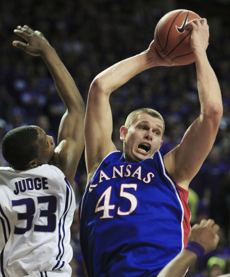 Photo - Kansas center Cole Aldrich (45) rebounds over Kansas State forward Wally Judge (33) during the first half of an NCAA college basketball game Saturday, Jan. 30, 2010, in Manhattan, Kan. (AP Photo/Orlin Wagner) ORG XMIT: KSOW104