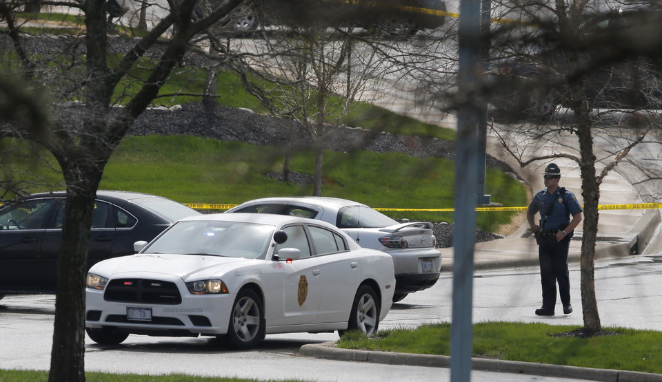 Photo - A Kansas State Trooper stands near the location of a shooting at the Jewish Community Center in Overland Park, Kan., Sunday, April 13, 2014. (AP Photo/Orlin Wagner)