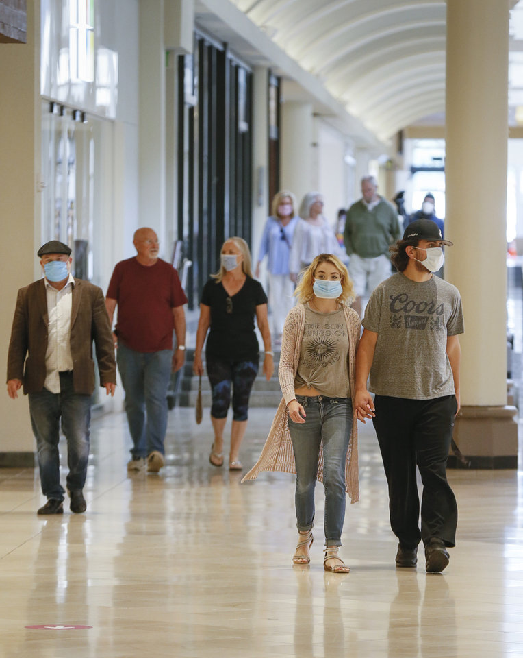 Photo - People walk through Penn Square Mall during the re-opening of the mall after being closed because of the coronavirus pandemic, in Oklahoma City, Friday, May 1, 2020. [Nate Billings/The Oklahoman]