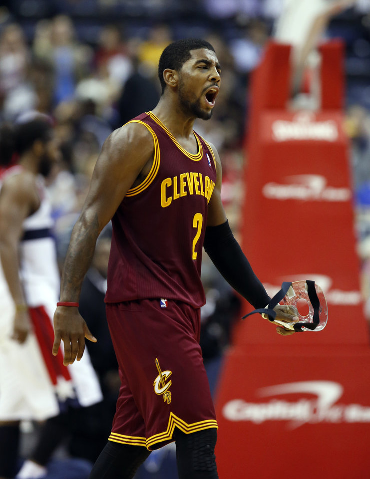 Photo - Cleveland Cavaliers guard Kyrie Irving (2) celebrates his shot during a timeout in overtime of an NBA basketball game against the Washington Wizards, Saturday, Nov. 16, 2013, in Washington. Irving had 41 points and the Cavaliers won 103-96. (AP Photo/Alex Brandon)