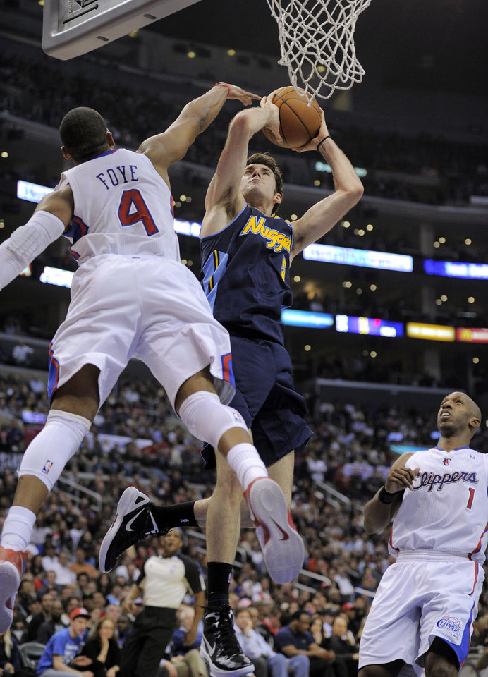 Photo -   Denver Nuggets guard Rudy Fernandez, center, of Spain puts up a shot as Los Angeles Clippers guard Randy Foye, left, defends and guard Chauncey Billups watches during the first half of an NBA basketball game, Thursday, Feb. 2, 2012, in Los Angeles. (AP Photo/Mark J. Terrill)