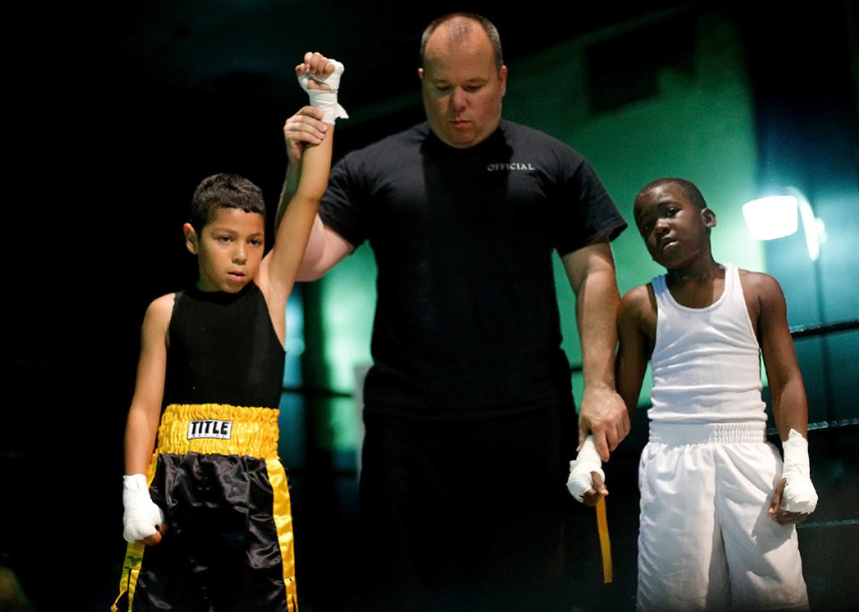 Photo -  Nine-year-old Chris Barba, of Edmond, at right, is declared the winner beside Roderick Tisdale, 10, of Pawhuska, after the pair's first fight at The Underground Arena in Oklahoma City, Saturday, June 15, 2013.