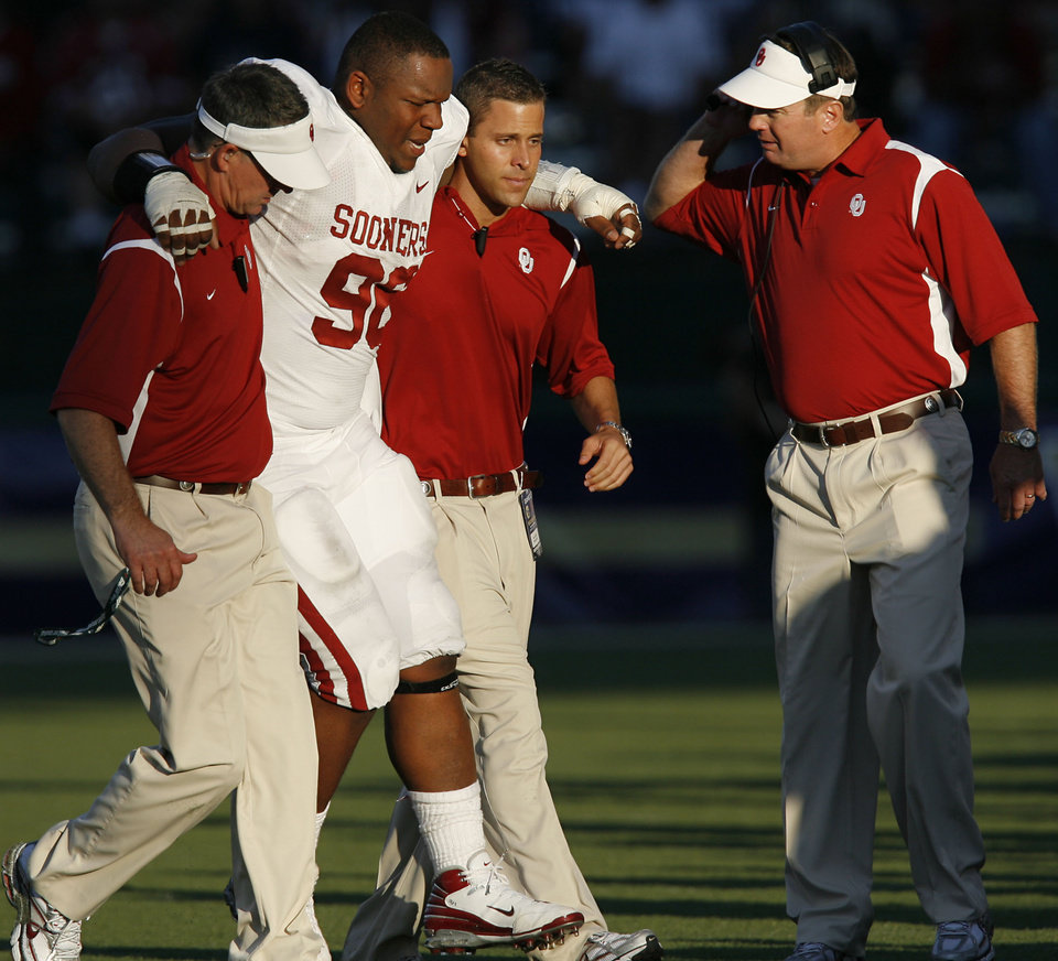 Photo - Coach Bob Stoops looks on as trainers help DeMarcus Granger (96) off the field with an injury during the first half of the college football game between the University of Oklahoma Sooners (OU) and the University of Washington Huskies (UW) at Husky Stadium on Saturday, Sep. 13, 2008, in Seattle, Wash. 