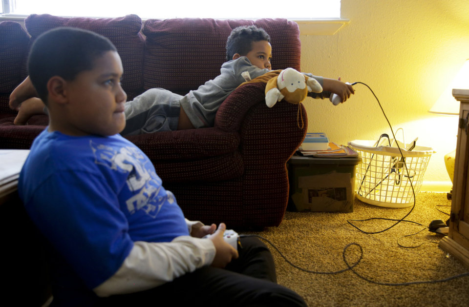 Photo -  Desha Bailey's sons, Jakobie Roberson, left, 10, and Isaiah Roberson, 6, play the video game
