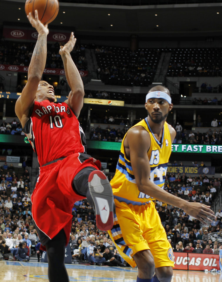 Photo - Toronto Raptors guard DeMar DeRozan, left, is fouled--as he drives the lane for a shot--by Denver Nuggets forward Corey Brewer in the first quarter of an NBA basketball game in Denver on Monday, Dec. 3, 2012. (AP Photo/David Zalubowski)
