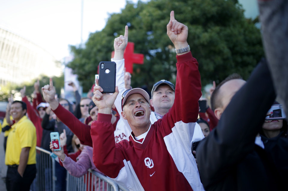 Photo - Fans cheer as Oklahoma arrives before the Red River Showdown college football game between the University of Oklahoma Sooners (OU) and the Texas Longhorns (UT) at Cotton Bowl Stadium in Dallas, Saturday, Oct. 12, 2019. [Sarah Phipps/The Oklahoman]