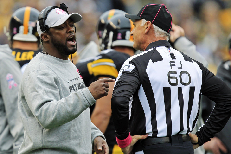 Pittsburgh Steelers head coach Mike Tomlin, left, talks with field judge Gary Cavaletto (60) during a timeout in the second quarter of an NFL football game against the Philadelphia Eagles in Pittsburgh, Sunday, Oct. 7, 2012. The Steelers won 16-14. (AP Photo/Gene J. Puskar)
