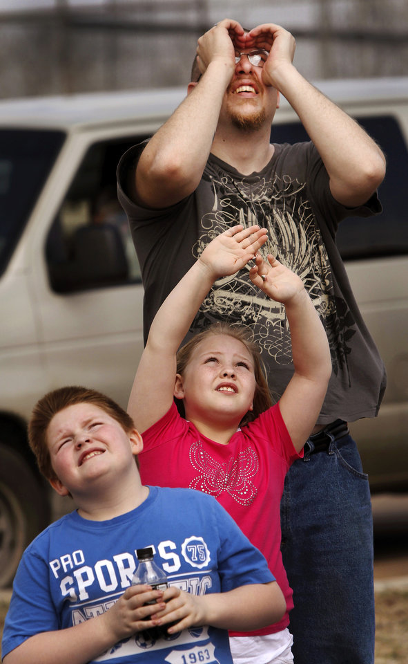 Jason Huhman and his children, Dawson, 8, and Chrissy, 9, look upward to watch the fireworks. An estimated 500 people came to Crosslin Park to watch a demonstration of daytime fireworks during the noon hour on Wednesday, Tuesday, March 14, 2012. The fireworks are a joint effort between Dentsu Tec, a Japanese production company and Enid fireworks manufacturer Western Enterprises to commemorate an 1883 U.S. patent for daytime fireworks. The fireworks consist of smoke in an array of colors and parachutes that are shot several hundred feet in the air before floating back to the ground. Photo by Jim Beckel, The Oklahoman