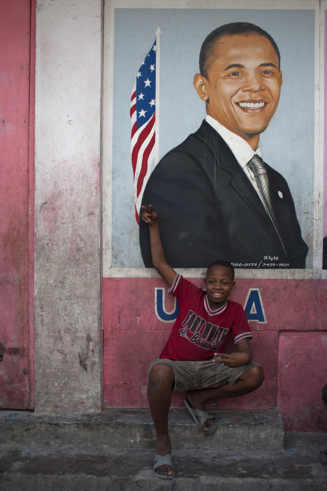 Resident Thony Jeff, 14, poses for pictures in front of an image depicting President Barack Obama in Petion-Ville, Haiti, Wednesday Nov. 7, 2012. Obama was re-elected for a second presidential term, defeating his Republican challenger, former Massachusetts Gov. Mitt Romney in Tuesday's election. (AP Photo/Dieu Nalio Chery)