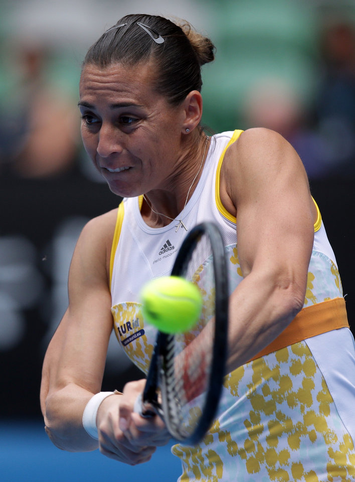 Photo - Flavia Pennetta of Italy makes a backhand return to Li Na of China  during their quarterfinal at the Australian Open tennis championship in Melbourne, Australia, Tuesday, Jan. 21, 2014.(AP Photo/Aaron Favila)