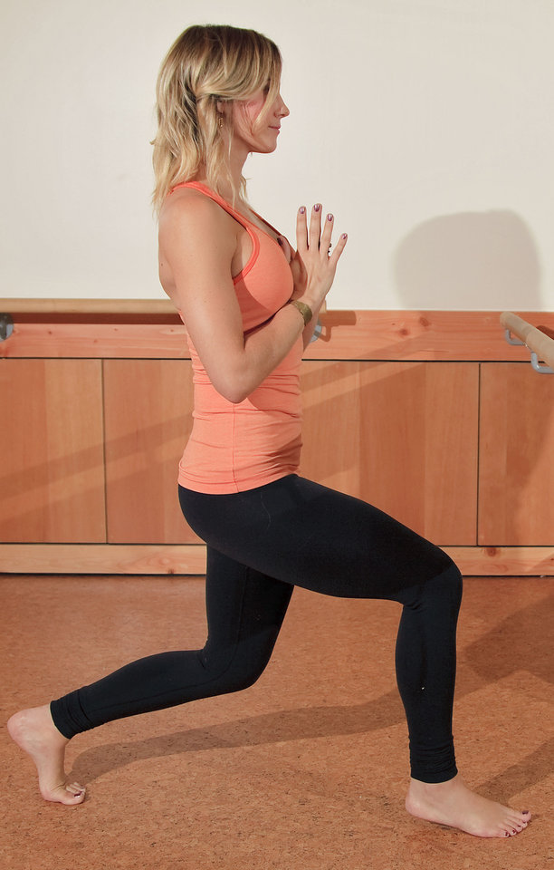 Andrea Mason, owner of Barre3, demonstrates Carousel Horse.  Stand tall, step one leg back and bend your front knee over your ankle. Your back knee is directly underneath your frontal hip bone, and your shoulders are stacked over your hips. This targets your quadriceps. Photo by Chris Landsberger, The Oklahoman. <strong>CHRIS LANDSBERGER</strong>