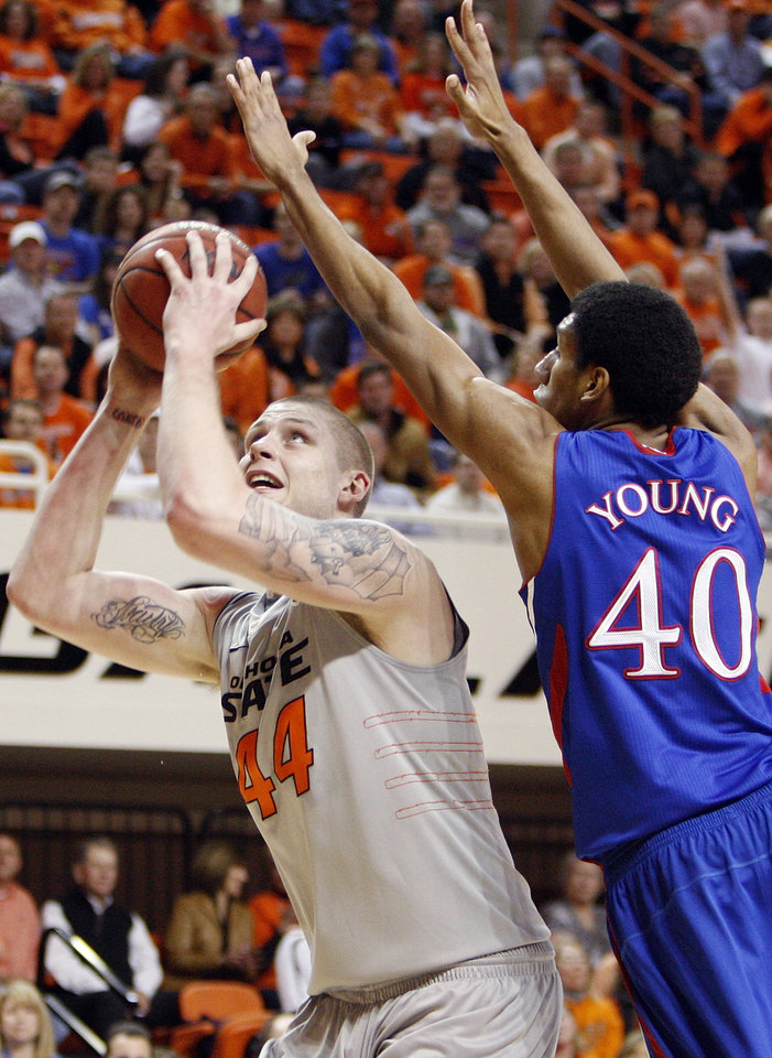 Photo - OSU's Philip Jurick (44) tries to shoot against KU's Kevin Young (40) in the first half during a men's college basketball game between the Oklahoma State University Cowboys and the University of Kansas Jayhawks at Gallagher-Iba Arena in Stillwater, Okla., Monday, Feb. 27, 2012. Photo by Nate Billings, The Oklahoman