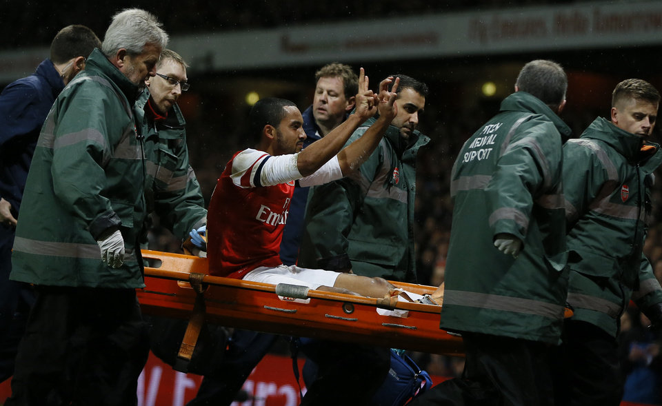 Photo - Arsenal's Theo Walcott, waves to the crowd as he is carried from the pitch on a stretcher after an injury during the English FA Cup third round soccer match between Arsenal and Tottenham Hotspur at the Emirates Stadium in London, Saturday, Jan. 4, 2014. (AP Photo/Kirsty Wigglesworth)