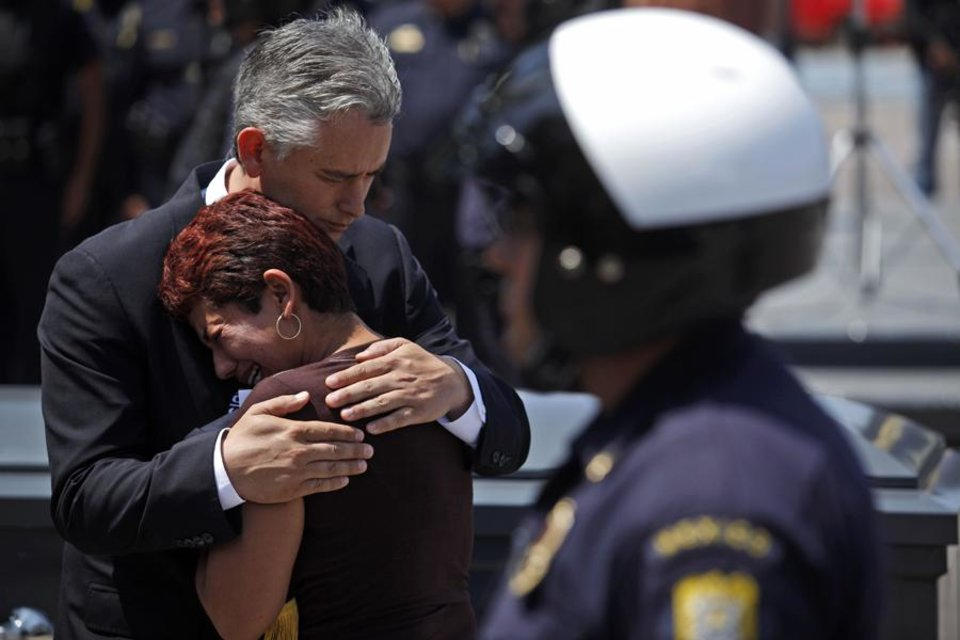 Photo -  Tijuana's Mayor Jorge Ramos comforts Celia Urdelia Medina wife of slain assistant municipal police chief Abel Salazar during his funeral in Tijuana, Mexico, Monday, May 18, 2009. Salazar was fatally shot Saturday when he was driving to his job at a police substation in Tijuana.(AP Photo/Guillermo Arias)