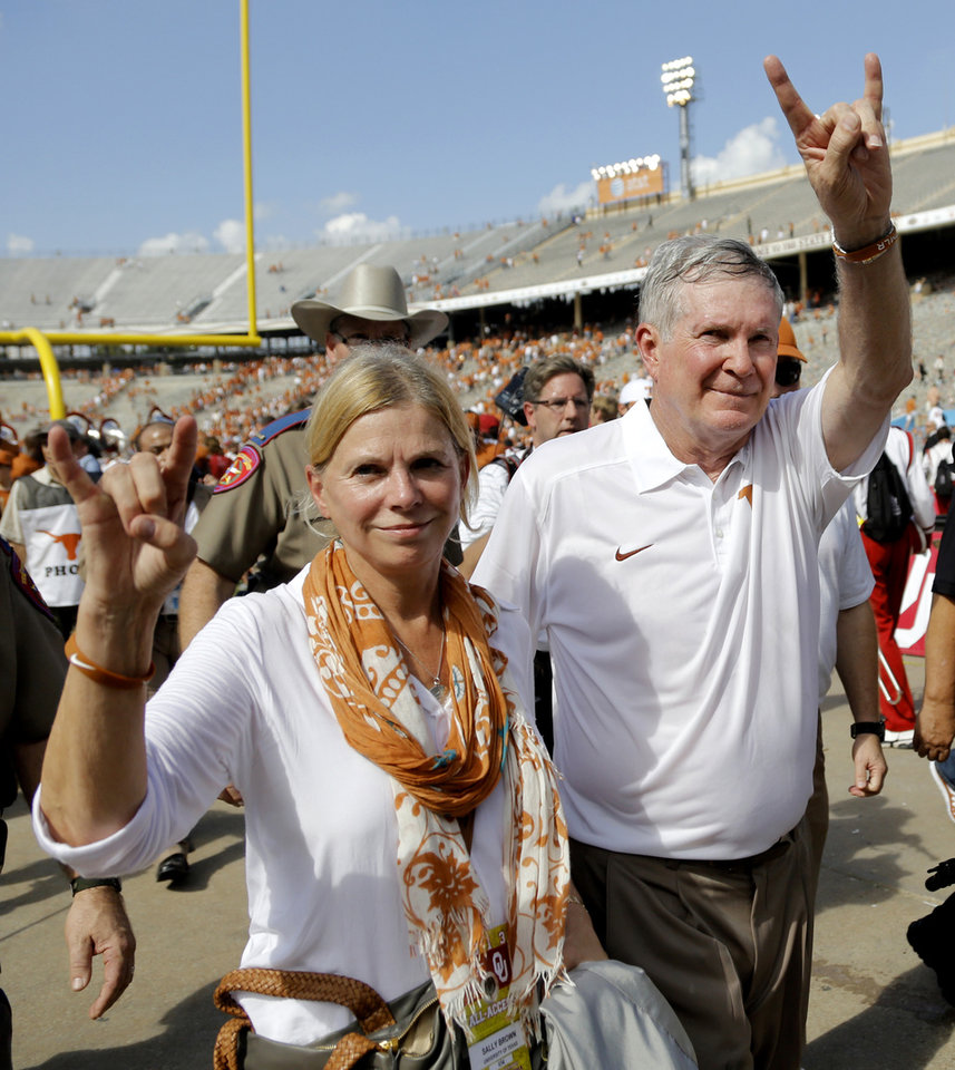 Photo - Texas coach Mack Brown walks off the field with his wife Sally as they salute the fans after the 36-20 win over Oklahoma during the Red River Rivalry college football game between the University of Oklahoma Sooners (OU) and the University of Texas Longhorns (UT) at the Cotton Bowl Stadium in Dallas, Saturday, Oct. 12, 2013. Photo by Chris Landsberger, The Oklahoman