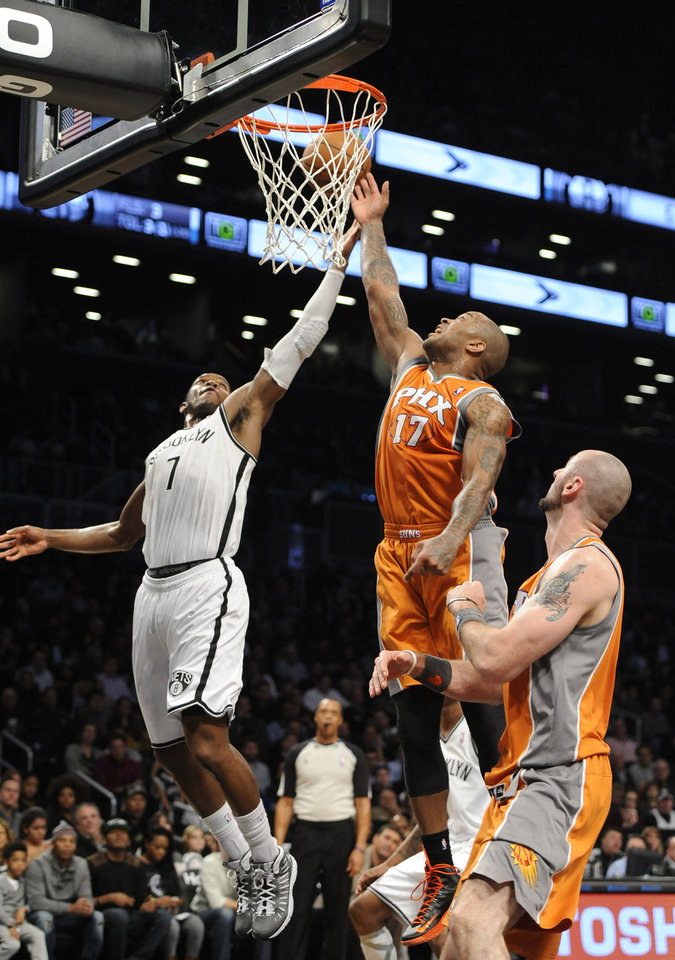 Brooklyn Nets' Joe Johnson (7) blocks the shot of Phoenix Suns' P.J. Tucker (17) as Marcin Gortat (4) watches at right in the second  half of an NBA basketball game on Friday, Jan., 11, 2013 at Barclays Center in New York. The Nets won 99-79. (AP Photo/Kathy Kmonicek)