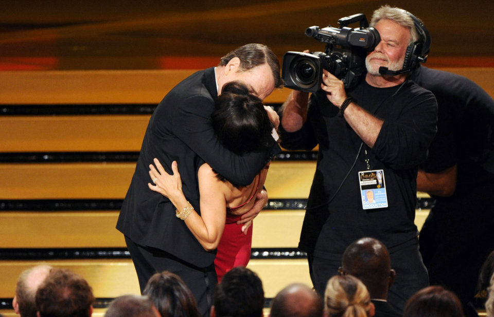 "Photo - Bryan Cranston kisses Julia Louis-Dreyfus, center front, as she accepts the award for outstanding lead actress in a comedy series for her work on ""Veep"" at the 66th Annual Primetime Emmy Awards at the Nokia Theatre L.A. Live on Monday, Aug. 25, 2014, in Los Angeles. (Photo by Chris Pizzello/Invision/AP)"