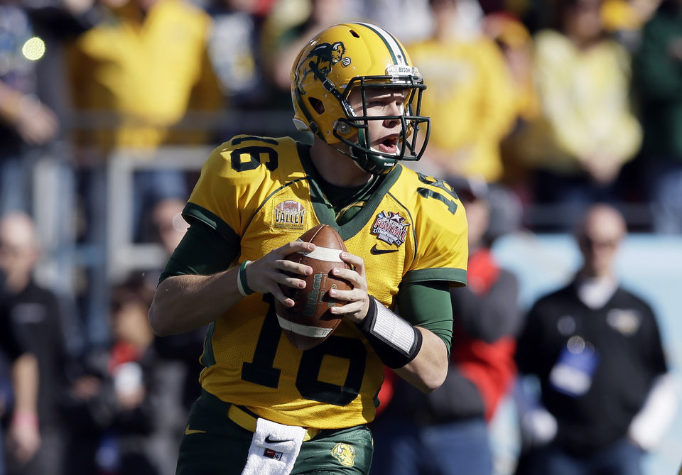 Photo - North Dakota State quarterback Brock Jensen drops back to pass in the first half of the FCS championship NCAA college football game against Towson, Saturday, Jan. 4, 2014, in Frisco, Texas. (AP Photo/Tony Gutierrez)