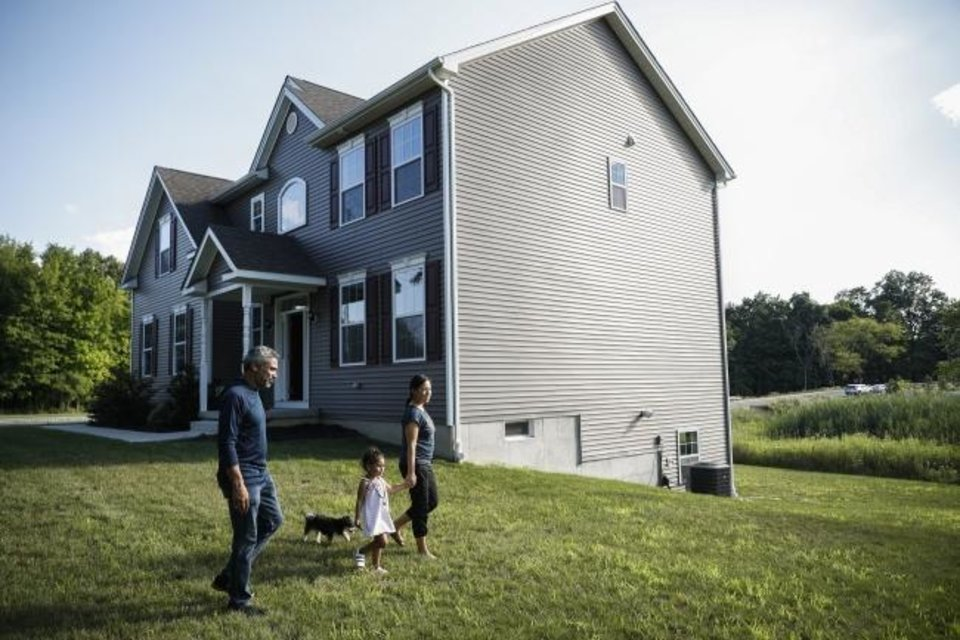 Photo -  Joyce Lilly, right, holds her granddaughter Paige's hand alongside her husband, Anil, and dog Max at their new home in Washingtonville, New York. [AP PHOTO]