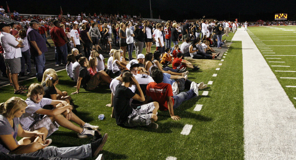 Photo - Fans line the sidelines during the high school football game between Mustang and Yukon at Yukon High School in Yukon, Okla., Friday, Sept. 3, 2010. Photo by Nate Billings, The Oklahoman