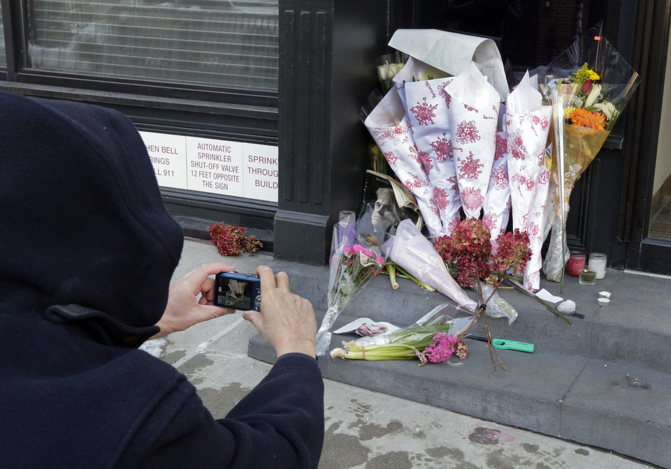 Photo - A passerby photographs the flowers placed outside the apartment building of actor Phillip Seymour Hoffman, in New York,  Tuesday, Feb. 4, 2014. Autopsy results are expected soon in the death of actor Phillip Seymour Hoffman but police say it may take longer to determine if the heroin found in his apartment contains additives designed intensify the high. (AP Photo/Richard Drew)