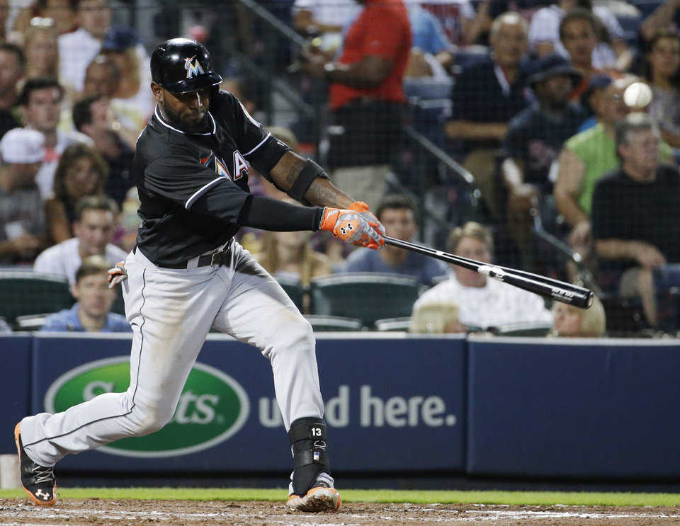 Photo - Miami Marlins' Marcell Ozuna singles to score teammate Casey McGehee in the sixth inning of a baseball game against the Atlanta Braves, Friday, Aug. 29, 2014, in Atlanta. (AP Photo/David Goldman)