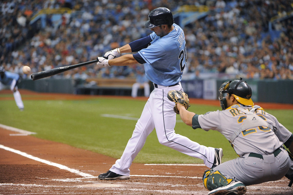 Photo -   Tampa Bay Rays'r Matt Joyce, left, hits a two-run single in front of Oakland Athletics catcher Anthony Recker during the first inning of a baseball game Sunday, May 6, 2012, in St. Petersburg, Fla. (AP Photo/Brian Blanco)