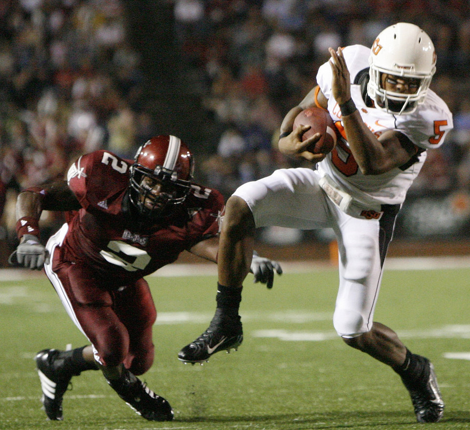 Photo - OSU's Keith Toston (5) tries to get away from Troy's Boris Lee in the first quarter during the college football game between the Troy University Trojans and the Oklahoma State University Cowboys at Movie Gallery Veterans Stadium in Troy, Ala., Friday, September 14, 2007. BY MATT STRASEN, THE OKLAHOMAN