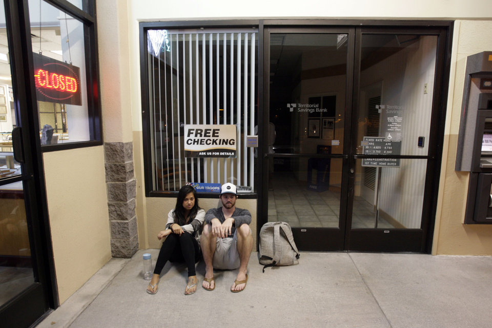 Photo - Jessica Teng, left, and John Parisik find shelter in a shopping center early Friday, March 11, 2011 in Kailua-Kona, Hawaii.  The Kailua-Kona couple was forced to evacuate their coastal condominium due to a tsunami warning following an earthquake in Japan. Tsunami waves spawned by a massive earthquake in Japan have hit Hawaii. The Pacific Tsunami Warning Center says Kauai was the first island hit early Friday by the tsunami, which was quickly sweeping through the Hawaiian Island chain. Officials predicted Hawaii would experience waves up to 6 feet. (AP Photo/Chris Stewart) ORG XMIT: HICS103