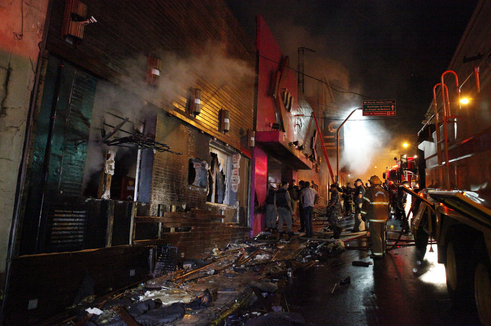 Photo - Firefighters work to douse a fire at the Kiss Club in Santa Maria city, Rio Grande do Sul state, Brazil, Sunday, Jan. 27, 2013. Firefighters say that the death toll from a fire that swept through a crowded nightclub in southern Brazil has risen to 180. Officials say the fire broke out at the club while a band was performing. At least 200 people were also injured. (AP Photo/Agencia RBS)