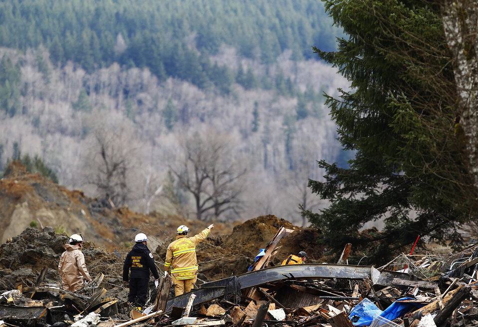 Photo - Searchers examine the area on the western edge of the mudslide where it covers Highway 530 Wednesday morning, March 26, 2014, east of Oso, Wash.  The debris field is about a square mile and 30 to 40 feet deep in places, and includes quicksand-like muck, rain-slickened mud and ice.   (AP Photo/The Herald, Mark Mulligan )