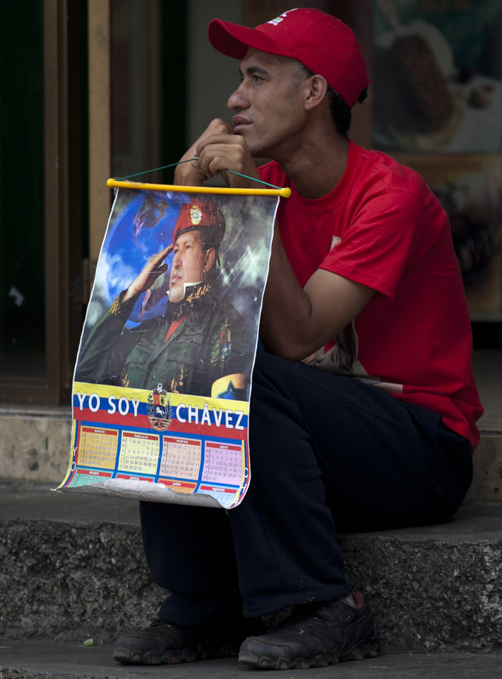A supporter of Venezuela's President Hugo Chavez holds a calendar with an image of Chavez near the military hospital in Caracas, Venezuela, Friday, Feb. 22, 2013. The government said that the ailing president was continuing unspecified medical treatments at the military hospital. Chavez's sudden return to Venezuela after more than two months of cancer treatments in Cuba has fanned speculation that the president could be preparing to relinquish power and make way for a successor and a new election. (AP Photo/Ariana Cubillos)