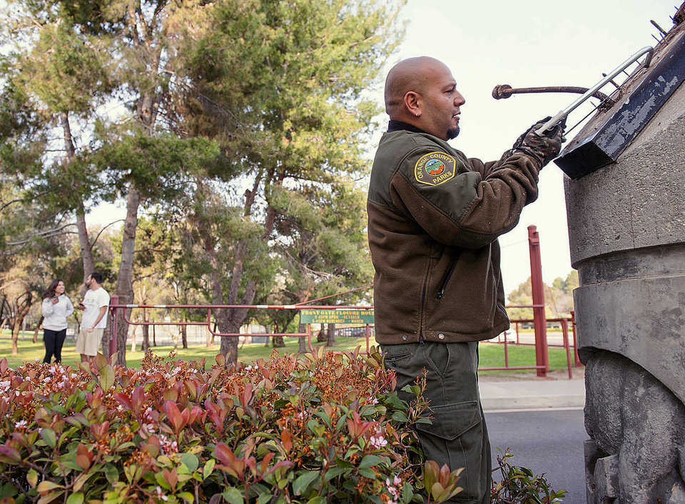 Photo - Orange County Parks grounds keeper Frank Amaro removes the supports to the sign at the entrance of Ralph B. Clark Regional Park in Buena Park in Fullerton, Calif.,  on Saturday, March 29, 2014,  morning after rangers discovered it fell off it's supports after an earthquake hit Orange County Friday night.   More than 100 aftershocks have rattled Orange County south of Los Angeles where a magnitude-5.1 earthquake struck Friday.  Despite the relatively minor damage, no injuries have been reported. (AP Photo/The Orange County Register, Ken Steinhardt)   MAGS OUT; LOS ANGELES TIMES OUT