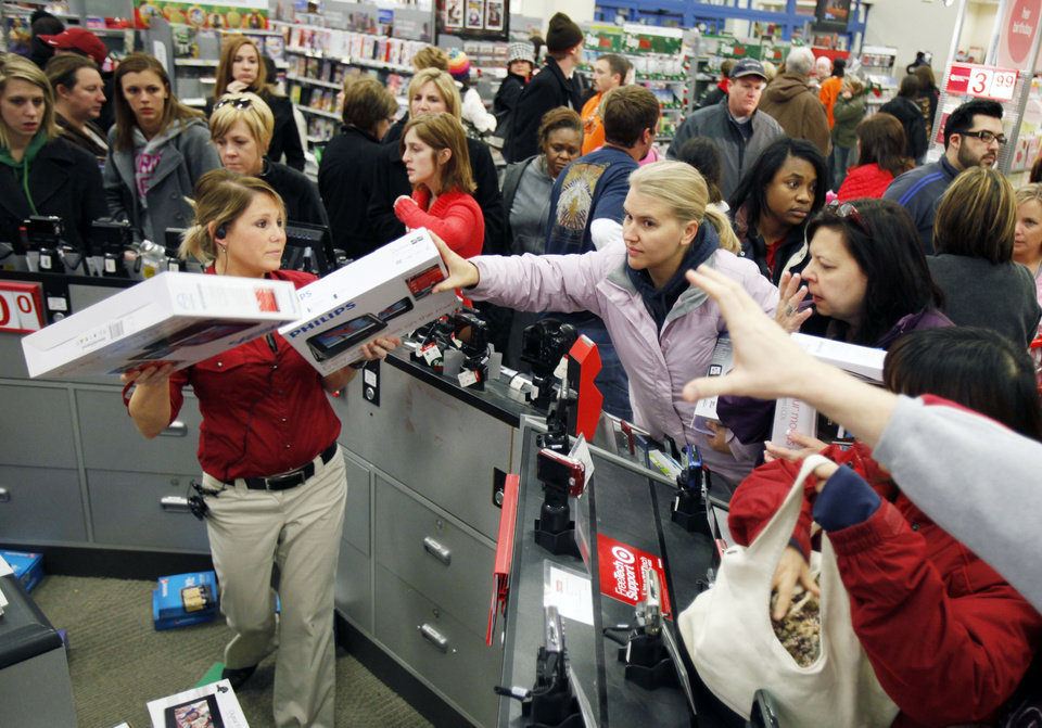 Electronics salesperson Lauren McKenzie passes out electronics to anxious shoppers during the 4 a.m. Black Friday shopping rush at the Target store at Quail Springs in Oklahoma City, Friday, Nov. 26, 2010. Photo by Paul Hellstern, The Oklahoman