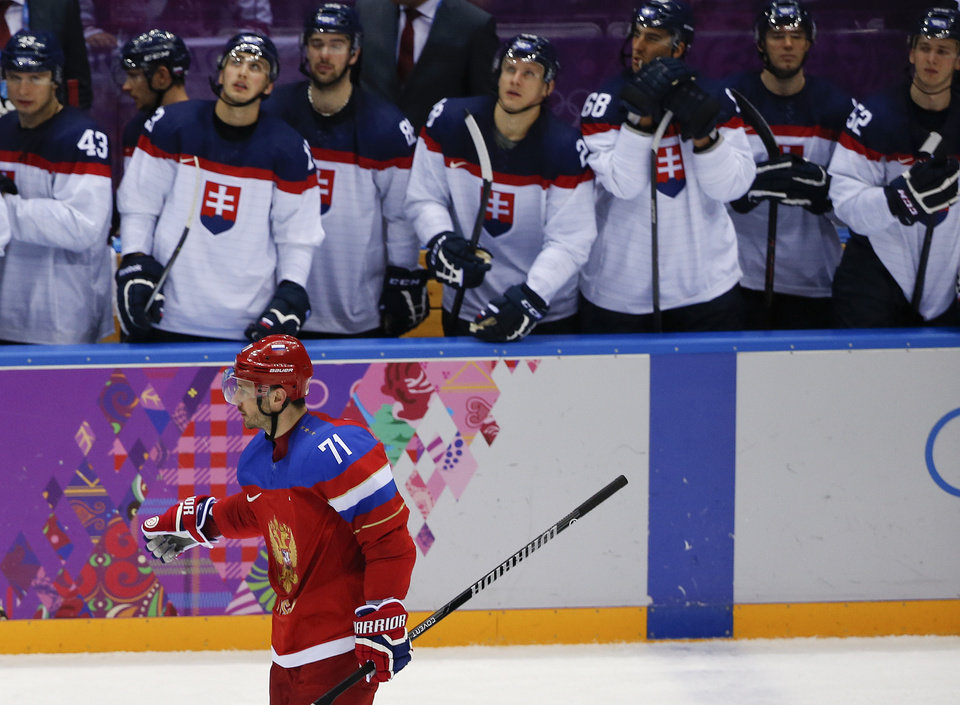 Photo - Russia forward Ilya Kovalchuk skates by the Slovakian bench after scoring the winning goal in a shootout of a men's ice hockey game at the 2014 Winter Olympics, Sunday, Feb. 16, 2014, in Sochi, Russia. Russia won 1-0. (AP Photo/Julio Cortez)