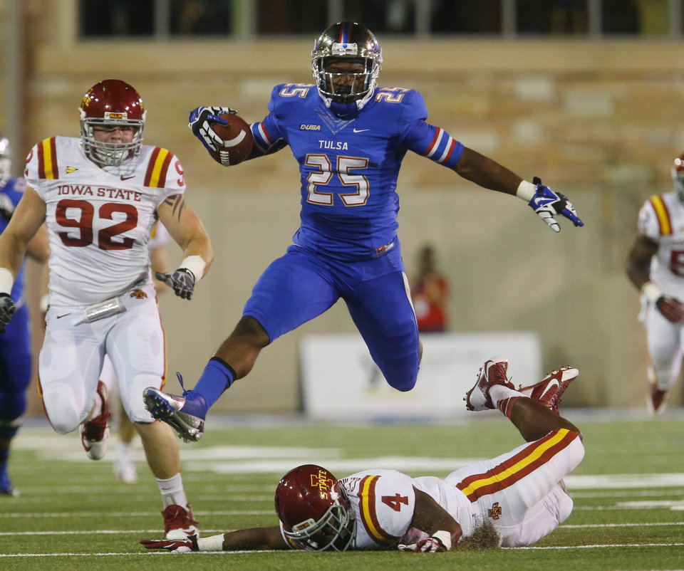 Photo - Tulsa's Ja'Terian Douglas (25) jumps over Iowa State's Sam Richardson (4) during the first half of an NCAA college football game, Thursday, Sept. 26, 2013 in Tulsa, Okla. (AP Photo/Tulsa World, Tom Gilbert)  ONLINE OUT; TV OUT; TULSA OUT