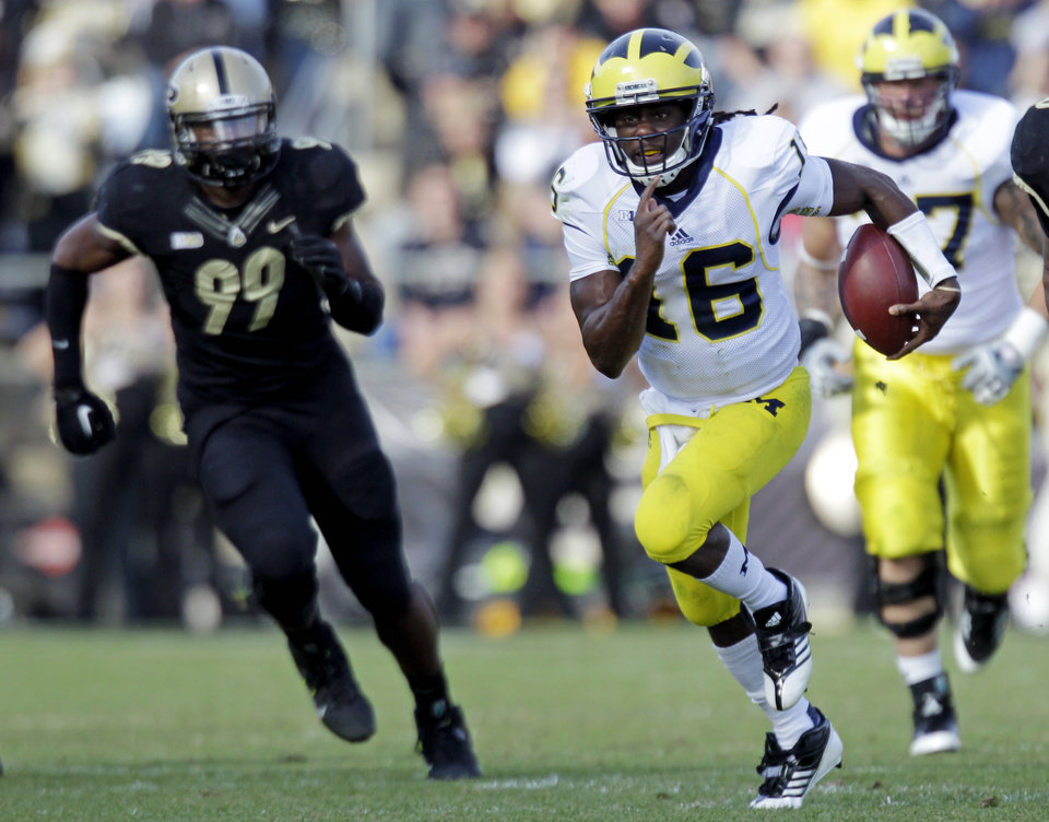 Photo -   Michigan quarterback Denard Robinson, center, gets past Purdue defensive end Ryan Russell (99) as he picks up 38 yards during the first half of an NCAA college football game in West Lafayette, Ind., Saturday, Oct. 6, 2012. (AP Photo/Michael Conroy)