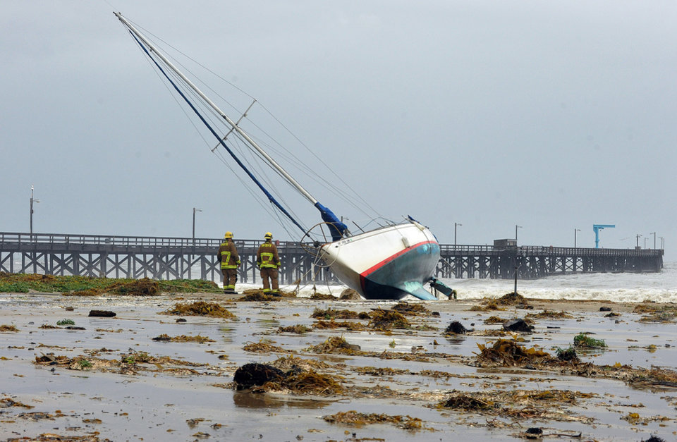 Photo - Santa Barbara County firefighters survey the scene after three sailboats washed ashore in Goleta, Calif., Saturday, March 1, 2014. The storm marked a sharp departure from many months of drought that has grown to crisis proportions for the state's vast farming industry. However, such storms would have to become common to make serious inroads against the drought, weather forecasters have said. (AP Photo/Santa Barbara News-Press, Mike Eliason)