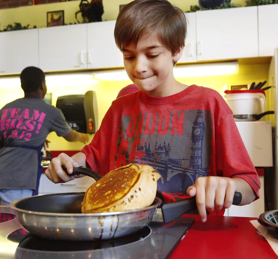 Zachary Jenkins, 11, struggles to keep his spatula underneath this pumpkin spice pancake as he flips it while competing in the Shawnee Mills'  Kids' Pancakes, Flapjacks and Griddle Cakes Contest at the Oklahoma State Fair on Saturday, Sep. 22, 2012. The event was held in the Creative Arts Building. Jenkins lives in Newalla and is a 6th grade home-schooled student.   Photo by Jim Beckel, The Oklahoman.