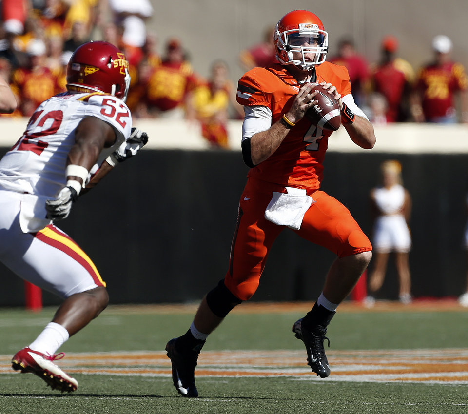Photo - Oklahoma State's J.W. Walsh (4) is scrambles as he is pressured by Iowa State's Jeremiah George (52) during a college football game between Oklahoma State University (OSU) and Iowa State University (ISU) at Boone Pickens Stadium in Stillwater, Okla., Saturday, Oct. 20, 2012. Photo by Sarah Phipps, The Oklahoman