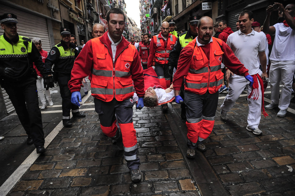 Photo - Medical assistants carry a participant injured during the running of the bulls with ''Torrestrella'' fighting bulls, at the San Fermin festival, in Pamplona, Spain, Monday, July 7, 2014. Revelers from around the world arrive to Pamplona every year to take part in some of the eight days of the running of the bulls glorified by Ernest Hemingway's 1926 novel