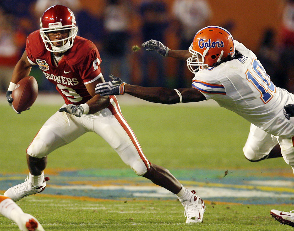 Photo - Oklahoma's Juaquin Iglesias (9) gets past Florida's Will Hill (10) in the first half during the BCS National Championship college football game between the University of Oklahoma Sooners (OU) and the University of Florida Gators (UF) on Thursday, Jan. 8, 2009, at Dolphin Stadium in Miami Gardens, Fla. 