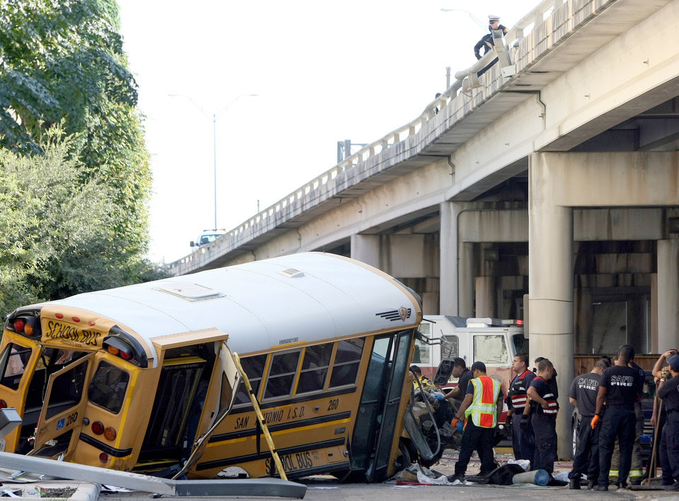 Photo -   Emergency responders clean up after a collision caused a San Antonio ISD school bus to crash through a guardrail and fall off an elevated portion of Interstate 37 near Houston Street in downtown San Antonio, Texas. The school bus plunged about 15 feet from a Texas expressway overpass to the doorstep of a hotel below, miraculously causing only non-life-threatening injuries to the child and two adults aboard. (AP Photo/San Antonio Express-News, Helen L. Montoya)