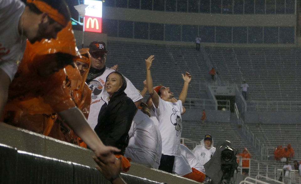 Photo - Fans wait out a weather delay during a college football game between the Oklahoma State Cowboys (OSU) and the Pitt Panthers at Boone Pickens Stadium in Stillwater, Okla., Saturday, Sept. 17, 2016. Photo by Sarah Phipps, The Oklahoman